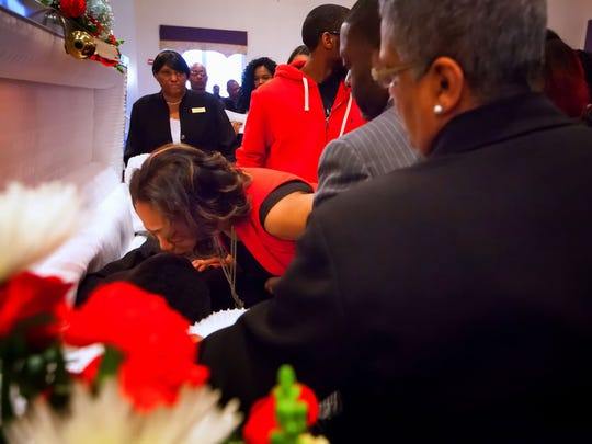 A tearful Shareece White, mother of William Rollins VI, gently kisses her son on the forehead as family members gather around his casket to say their last good-byes.