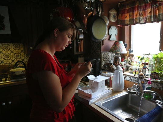 Sophia Walsh, an environmental health specialist with the Cerro Gordo health department, collects a sample of Jack and Sandy Davis' water on Tuesday, August 9, 2016, in Clear Lake. Jack and Sandy have their water tested twice a year after discovering their well water was contaminated with arsenic.