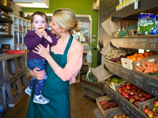 Grocer holding daughter in store