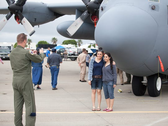 US Air Force Master Sergeant Keith Lafontaine takes a picture for Adelaida Andrade (left), of Edinburg and her friend Marissa DeLaGarza, from Corpus Christi in front of the US Air Force Reserve HC-130H2 on Saturday at the 2015 Wings Over South Texas Airshow at Naval Air Station Corpus Christi.