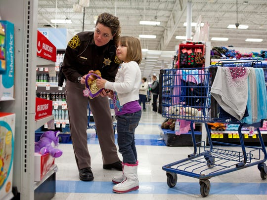 Olivia Wentz, 7, looks at toys with St. Clair County Sheriff's Deputy Keri Jenuwine during Shop with a Cop Tuesday at Meijer in Fort Gratiot.