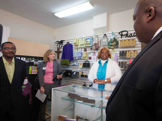 Officials visit Harvest Christian Retail Store owned by Suzette Flemming (center).