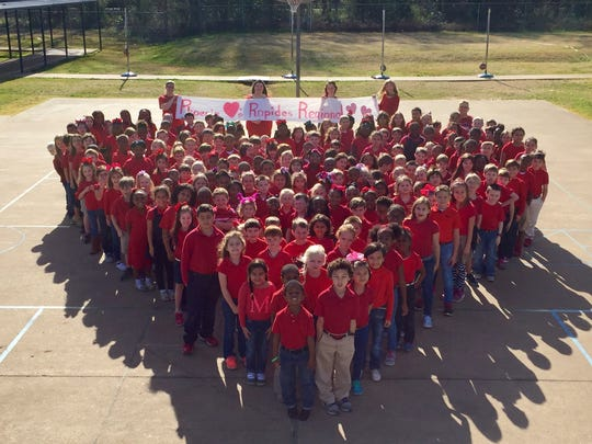 """Phoenix Magnet Elementary students stand in a heart with a sign that reads """"Phoenix loves Rapides Regional."""" The school is sending handmade Valentine's Day cards to patients at the hospital."""