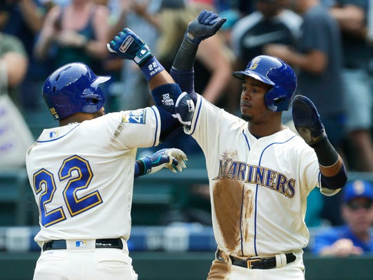 Seattle Mariners Robinson Cano (22) is greeted at the plate by Jean Segura after Cano hit a two-run home run to score Segura in a 2017 game.