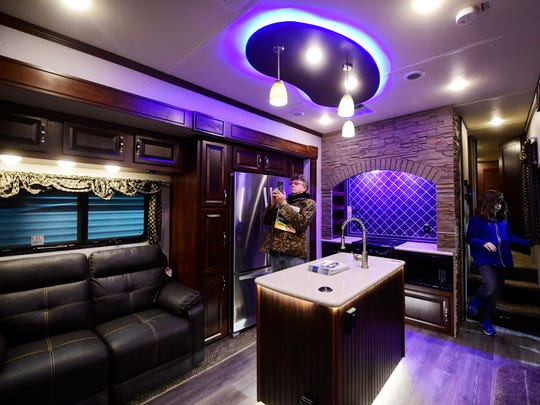 The kitchen/living room of the Vengeance Touring Edition 5th wheel has a decorative backsplash, full-size refrigerator, an island and mood lighting. Photo taken at the York RV Show at the York Expo Center in West Manchester Township Saturday, March 11, 2017.