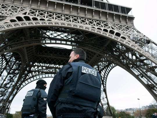 Police forces on patrol pass under the closed Eiffel Tower in Paris, France, Saturday, Nov. 14.