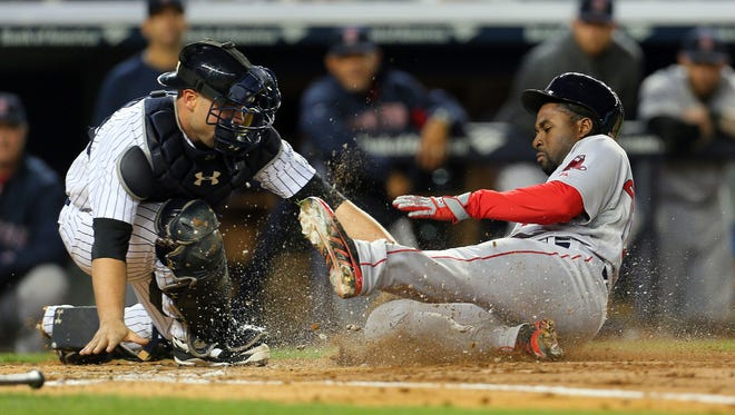 Yankees catcher Brian McCann tags out Boston Red Sox runner Jackie Bradley Jr. to end the top of the second inning.