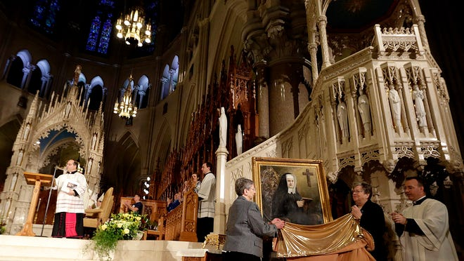 A painting of Sister Miriam Teresa Demjanovich is presented during a beatification ceremony at Cathedral Basilica of the Sacred Heart, Saturday, Oct. 4, 2014, in Newark, N.J. Demjanovich, who died in 1927 at age 26, is credited with curing Michael Mencer's eye disease as a boy when he was given a lock of the nun's hair and prayed to her. The ceremony moves Demjanovich a step closer to sainthood with her beatification as it is the third in a four-step process. (AP Photo/Julio Cortez)