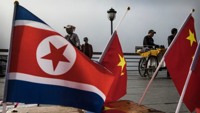 Chinese vendors sell North Korea and China flags on the boardwalk next to the Yalu river in the border city of Dandong, Liaoning province, northern China across from the city of Sinuiju, North Korea on May 24, 2017 in Dandong, China.