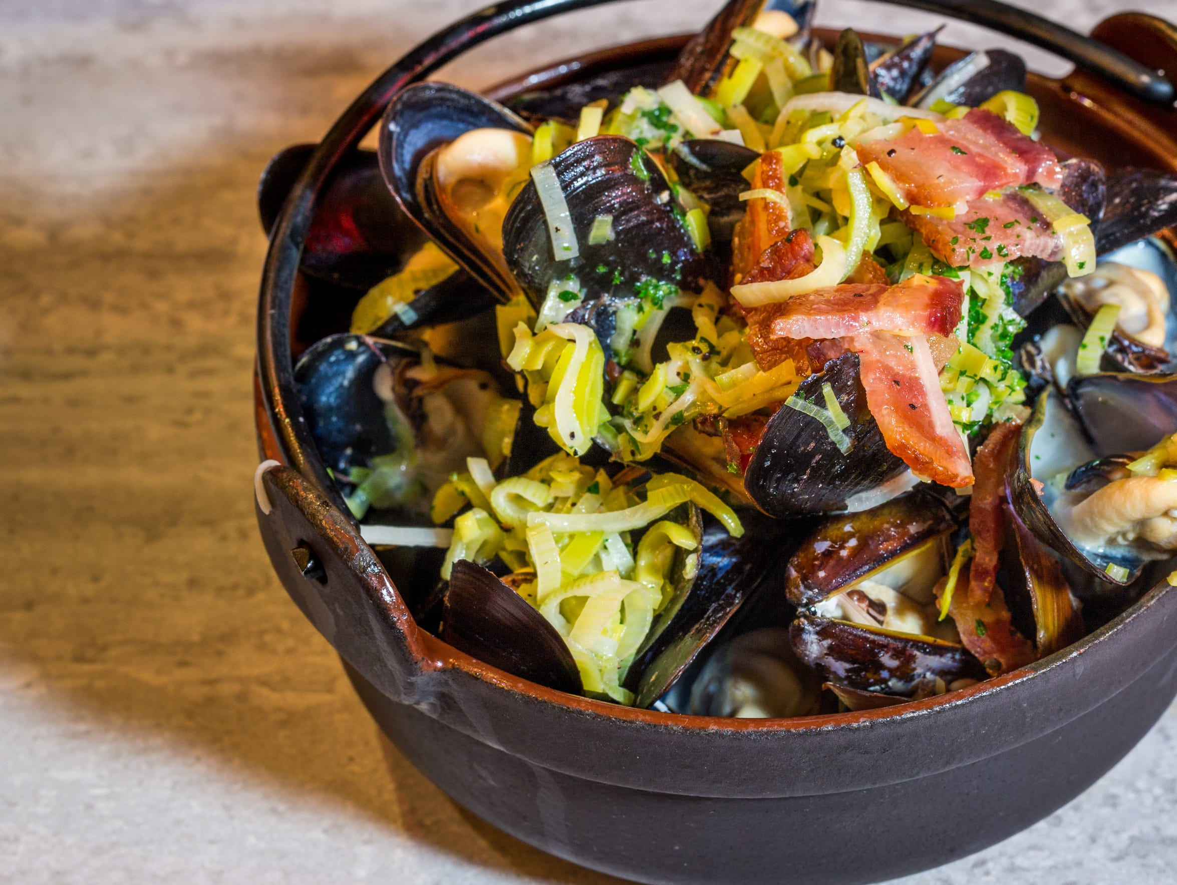A crock brims with mussels, leaks and salty pops of