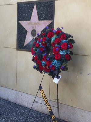 A wreath of flowers was placed at Muhammad Ali's Walk of Fame star, which is actually on the wall (as opposed to the ground).
