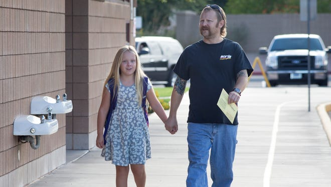 Chandler resident Scott Betcher arrives at Hull Elementary School Tuesday (Aug. 26, 2014) in Chandler to drop off his ballot at the polling place with his daughter, Leah. Byline: