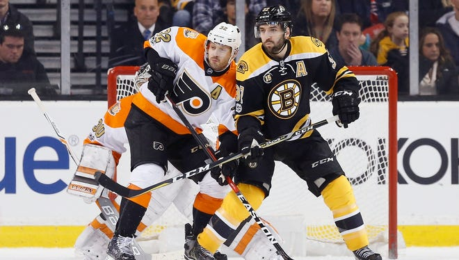 The Flyers' Mark Streit defends against Boston Bruins' Patrice Bergeron.