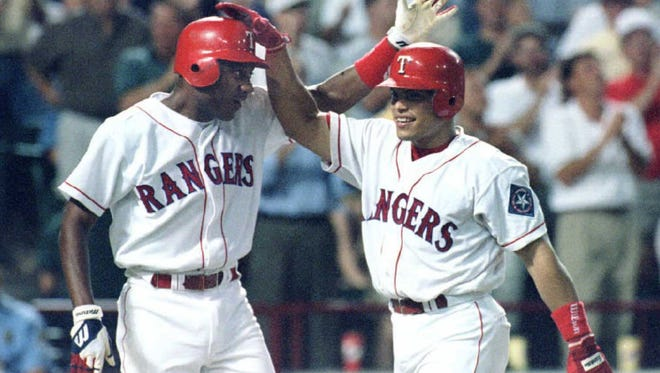 """Ivan""""Pudge""""Rodriguez of the Texas Rangers (R) is congratulated following his second home run of the night against the Cleveland Indians. At left is teammate Darryl Hamilton who scored on the homer."""