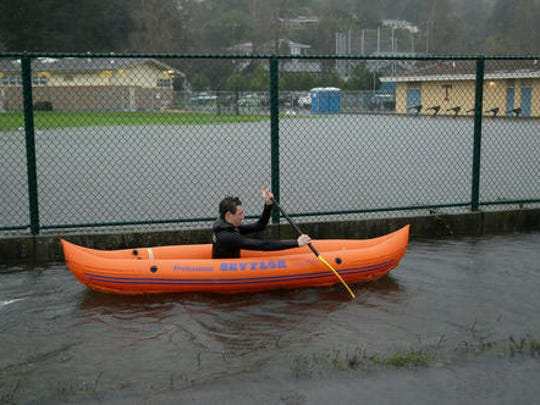 FILE - In this Dec. 15, 2016, file photo, Julian LePelch paddles his kayak past a flooded field at Tamalpais High School in Mill Valley, Calif. California's first winter storm of 2017 will shed welcome rain over the rivers, pumps and pipes that move California's water from north to south, and may open a new era of tensions over where that water goes, under a new federal law dictating that the state's farmers get the biggest possible share.