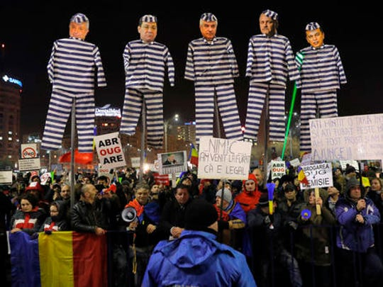 """Demonstrators carry puppets depicting, left to right, Justice Minister Floring Lordache, former Prime Minister Victor Ponta, head of the senate Calin Popescu Tariceanu, leader of the social democratic party Liviu Dragnea, and Prime Minister Sorin Grindeanu during a protest in Bucharest, Romania, Friday, Feb. 3, 2017. Romania's political crisis is deepening over a government decree that may benefit rich and powerful people convicted of corruption. Central banner reads: """"we came to steal because it is legal""""."""
