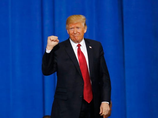 President Donald Trump raises his fist after speaking