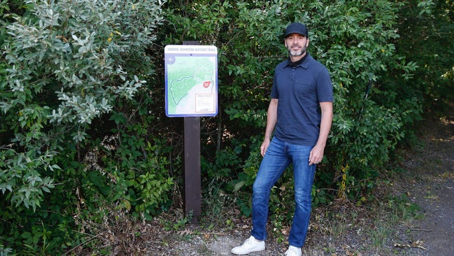 NASCAR driver Jimmie Johnson is pictured next to a map showing the Jimmie Johnson Nature Trail at Michigan International Speedway.