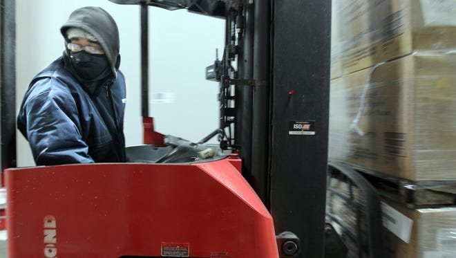 His face shielded from a temperature of -10 degrees by a balaclava, Michael Lastic operates a fork lift in Wornick Foods' new cold storage facility, which features both refrigeration and sub-zero areas to store food for military and major consumer companies.