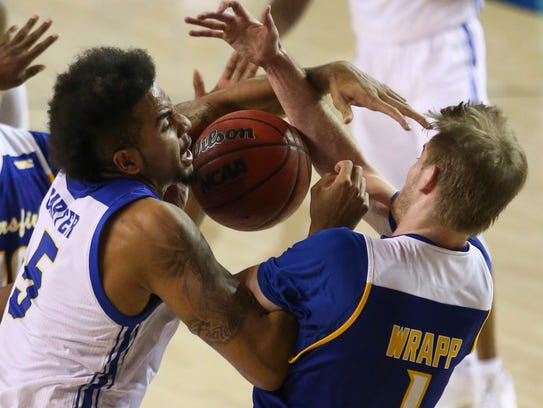 Delaware's Eric Carter (left) is fouled as he moves