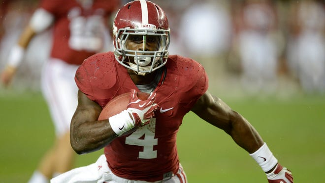Alabama running back T.J. Yeldon (4) carries the ball for a touchdown during the third quarter Saturday against LSU at Bryant-Denny Stadium.