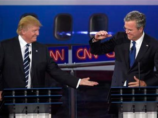 Republican presidential candidate, businessman Donald Trump, left, and Jeb Bush slap hands near the finish of the CNN Republican presidential debate at the Ronald Reagan Presidential Library and Museum on Wednesday, Sept. 16, 2015, in Simi Valley, Calif.