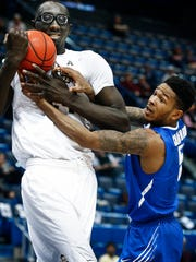 "University of Memphis guard Markel Crawford (right) tries to grab a rebound from Central Florida center Tacko Fall. ""We ran into a pretty tough wall,"" Crawford said after the game. ""Sometimes, it just happens."""