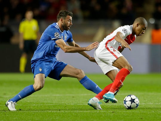 Juventus' Andrea Barzagli, left, challenges for the ball with Monaco's Kylian Mbappe during the Champions League semifinal first leg soccer match between Monaco and Juventus at the Louis II stadium in Monaco, Wednesday, May 3, 2017. (AP Photo/Claude Paris)