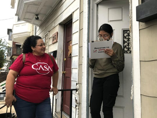 Mirna Orellana, left, a community organizer from the nonprofit group We Are Casa, answers questions as Karyme Navarro fills out a voter registration form in York City on Sept. 30, 2019. Democrats are counting on Hispanics so enraged by President Donald Trump's anti-immigrant rhetoric that they'll turn out in force to deny him a second term, but Trump's reelection campaign has launched its own Hispanic outreach efforts in non-traditional places like Pennsylvania, arguing that even slim gains could decide the 2020 race. (AP Photo/Will Weissert)