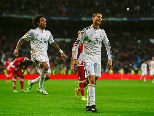 Real Madrid's Cristiano Ronaldo, center right, celebrates his goal with teammate Marcelo during a Spanish La Liga soccer match between Rayo Vallecano and Real Madrid at the Santiago Bernabeu stadium in Madrid, Spain, Saturday, Nov. 8, 2014. (AP Photo/Andres Kudacki)