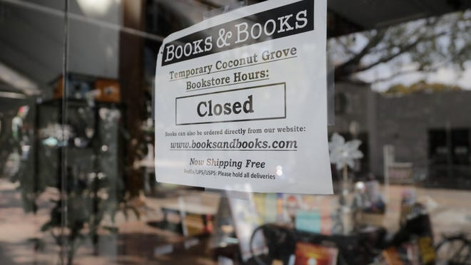 A sign on locally owned business Books & Books says the store is closed during the coronavirus pandemic, Thursday, April 9, 2020, in Miami. With 6.6 million people seeking unemployment benefits last week, the United States has reached a grim landmark: roughly one in 10 workers have lost their jobs in just the past three weeks to the coronavirus outbreak.