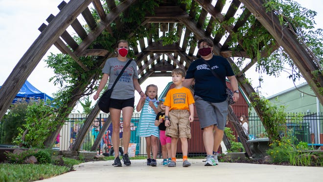 From right, Ann Williamson, Brady Wiebel, 6, Grace Wiebel, 2, Avery Quakenbush, 4, and Erin Quakenbush enter through an archway at the Kansas Children's Discovery Center on Thursday morning.