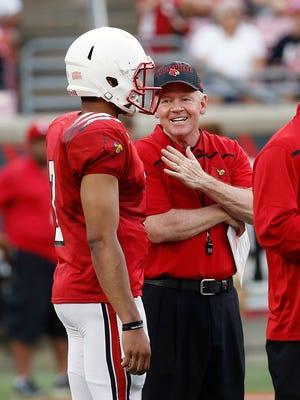 Louisville's Bobby Petrino shares a laugh with quarterback Reggie Bonnafon.  April 17, 2015
