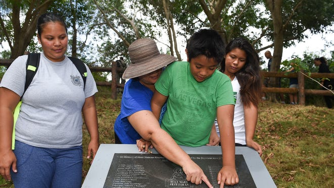 Descendants of Juan Inocencio Topasna look for his name on a memorial plaque at the Faha Massacre Site in Merizo on July 15, 2017.