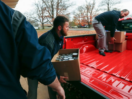 Kyle Goodman, right, and Tyler Nation, center, both of Reliable Chevrolet, unload the last boxes of donated food from the back of a Silverado pick-up truck at Grand Oak Baptist Mission Center on Tuesday, Nov. 22, 2016.