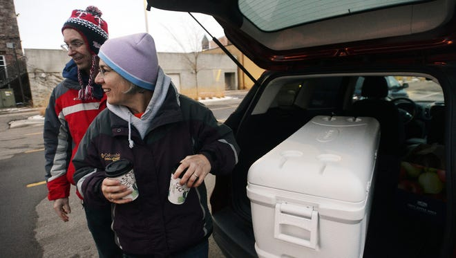 Shawn and Lynn Culey of Sunnycrest United Methodist Church hand out cups of scalloped potatoes and ham in the Raven Industries parking lot as part of the Nightwatch Canteen, which provides hot meals for anyone in need on Sunday nights.