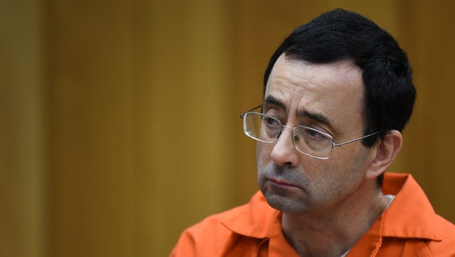 Larry Nassar listens as Rachael Denhollander gives her victim impact statement Friday, Feb. 2, 2018, in Eaton County Circuit Court, the second and final day of victim impact statements in Judge Janice Cunningham's courtroom in Charlotte, Mich.   He will be sentenced Monday. [MATTHEW DAE SMITH/Lansing State Journal]