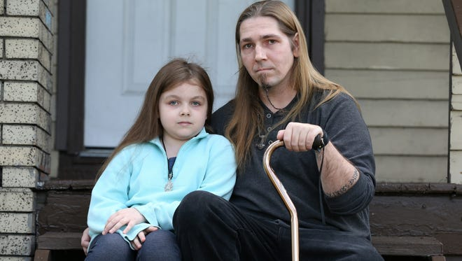 Lilith O'Neill, 9, and her father, Joseph O'Neill, on the porch of their Rochester home. Lilith hasn't been in school since the City School District rejected O'Neill's request for a religious exemption to the chicken pox vaccine.