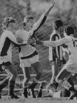 On Nov. 4, 1984, McNicholas's Keith Miller, center, is congratulated by teammates Rick Ziemba, left, and Tom Fermann after scoring the winning goal in Saturday's Ohio Class A-AA boys' soccer championship.