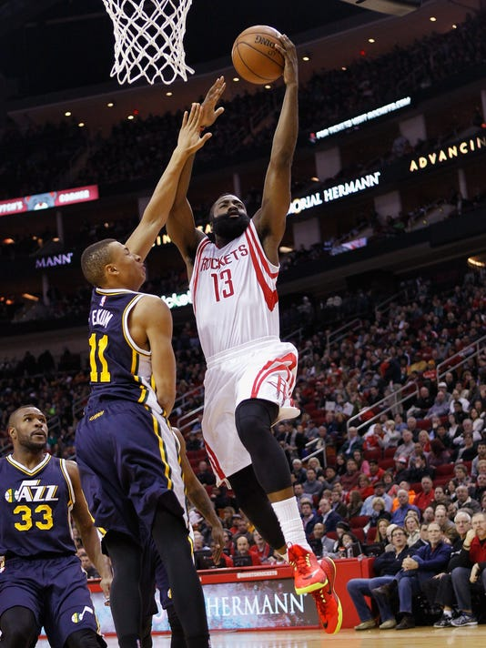 Houston Rockets guard James Harden (13) drives to the basket on Utah Jazz guard Dante Exum (11) during the first half of an NBA basketball game Saturday, Jan. 10, 2015, in Houston. (AP Photo/Bob Levey)