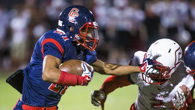 Centennial High School's David McGriff stiff arms Chaparral High School's Parker Walton during first half of action against Chaparral High School, at Centennial, Friday, October 9, 2015.