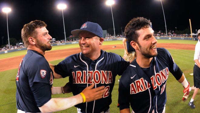 Arizona coach Jay Johnson, center, celebrates with Cody Ramer, left, and Cesar Salazar after Arizona defeated Mississippi State 6-5 in 11 innings in an NCAA college baseball tournament super regional game in Starkville, Miss., Saturday, June 11, 2016.
