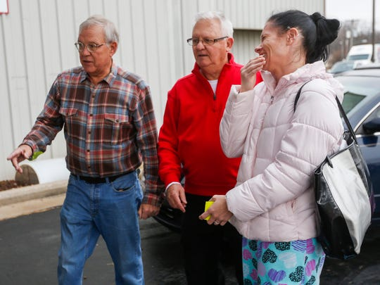 Leigh Gardner laughs after Don Golik, left, and Brad Hoppes loaded gifts into her car during the Share Your Christmas distribution day at Crosslines on Tuesday, Dec. 19, 2017.