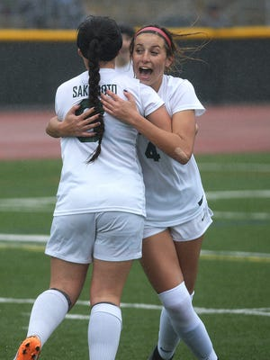 Zoe Hasenauer (right) is congratulated by Jenna Sakamoto after scoring a goal during Royal's 4-0 playoff win over Serrano at home Tuesday.
