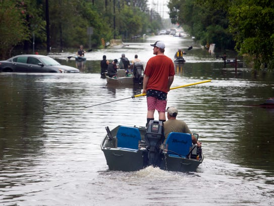 People in a boat make their way down a road in Dickinson,