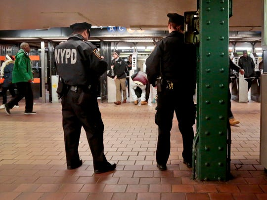 New York City police officers observe commuters using turnstiles at a Harlem subway station.