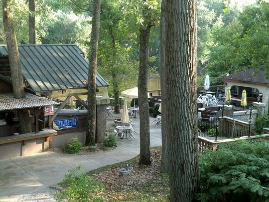 The back yard at Kreimer's slopes down to the banks of the Miami River with lots of large trees.