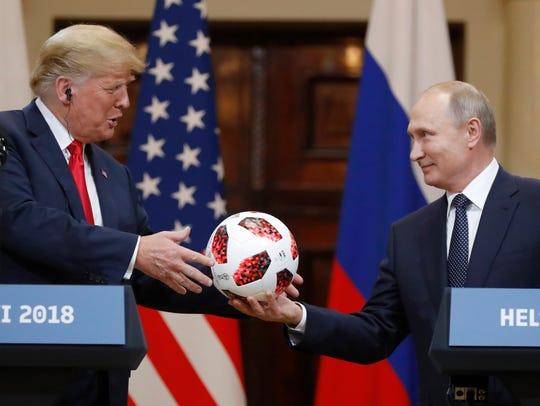 Russian President Vladimir Putin gives a soccer ball