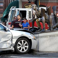 A two-car accident caused this driver to crash into the John Wooden statue at the Monday, October 5, 2015, afternoon at the corner of Meridian and Georgia Streets downtown Indianapolis.