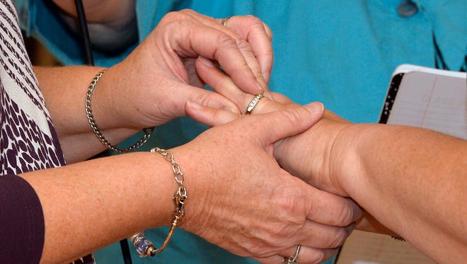 Karen Roberts, left, places a wedding band on the finger of her partner April Miller as they renew their vows in a public ceremony, Saturday, Oct. 24, 2015, in Morehead, Ky. Miller and Roberts were the plaintiffs in a suit filed against Rowan County Clerk Kim Davis by the American Civil Liberties Union in an attempt to have her office issue marriage licenses.